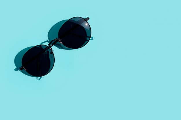 青色の背景にサングラス。コピースペース