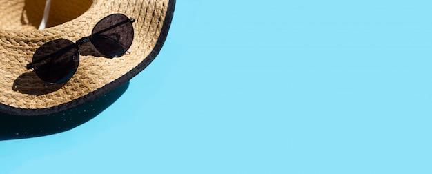 青の背景にサングラスをかけた帽子。夏の休日のコンセプトをお楽しみください。