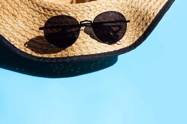 帽子と青の背景にサングラス。夏の休日のコンセプトをお楽しみください。