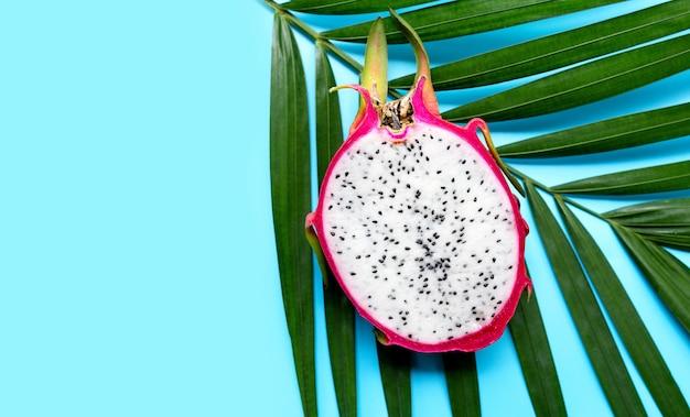 Спелый драконий фрукт или питахайя на тропических пальмовых листьях. вид сверху