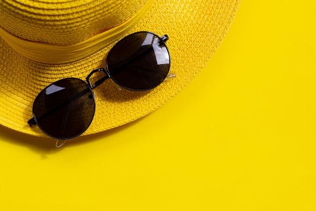 黄色の背景に夏帽子のサングラス。休日のコンセプトをお楽しみください。
