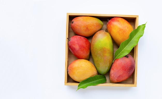 トロピカルフルーツ、マンゴー白い背景の上の木箱。
