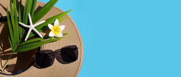 青の背景にサングラスをかけた夏帽子。休日のコンセプトをお楽しみください。