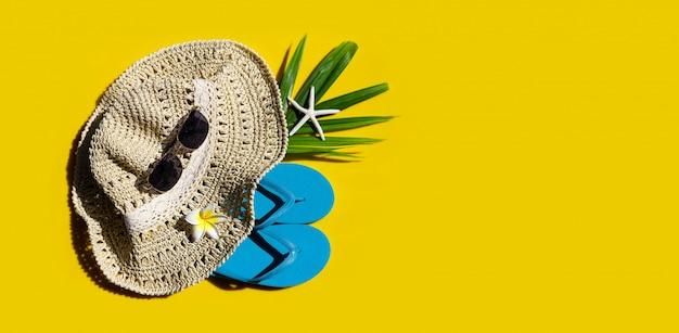 黄色の背景にサングラスをかけた夏帽子。休日のコンセプトをお楽しみください。