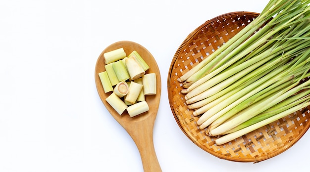 分離された白の木製竹脱穀バスケットで新鮮なレモングラスと木のスプーンでレモングラスのスライス。コピースペース