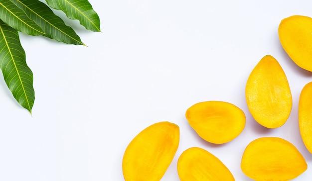 トロピカルフルーツ、分離した白の葉とマンゴーのスライス。コピースペース