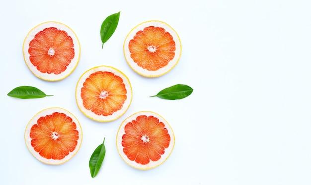 Высокое содержание витамина с. сочные дольки грейпфрута с зелеными листьями на белом фоне.