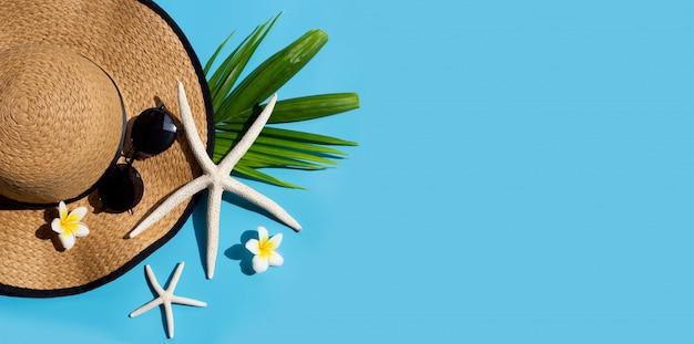 青の背景にサングラスをかけた夏帽子。休日のコンセプトをお楽しみください。コピースペース