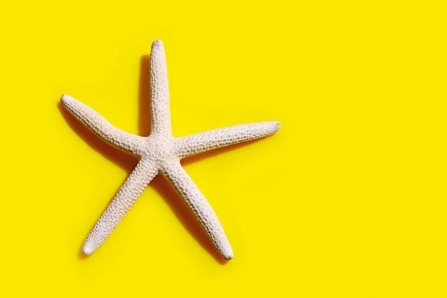 黄色の背景にヒトデ。夏の休日のコンセプトをお楽しみください。上面図