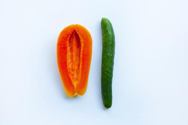 Огурец и папайя на белом фоне. сексуальная концепция.