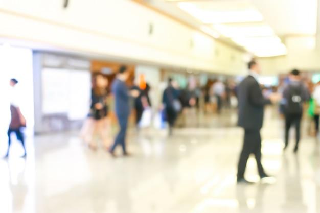 立ち上がってロビーを歩いているビジネス人々の活動がぼやけています。