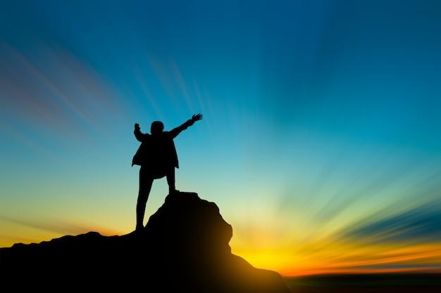 空と太陽の光の成功、リーダーシップ、人々の概念上の山の頂上の男のシルエット