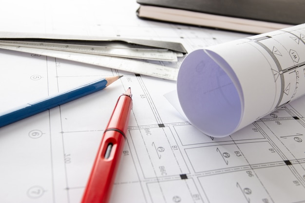 Рулоны архитектурных чертежей и планов домов на столе и инструменты рисования архитектора.
