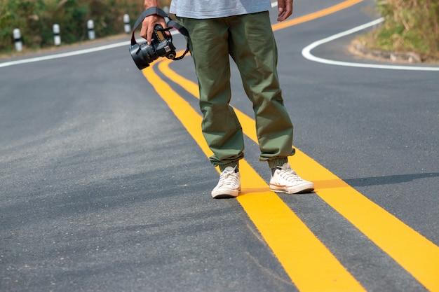 カメラを手に持って道を歩いている写真家