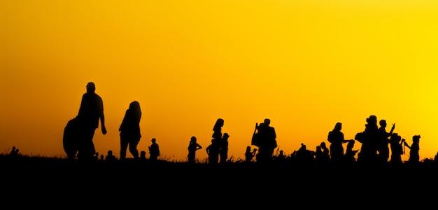 多くの観光客のシルエットは、日没時に山の頂上でスマートフォンで写真を撮っています。