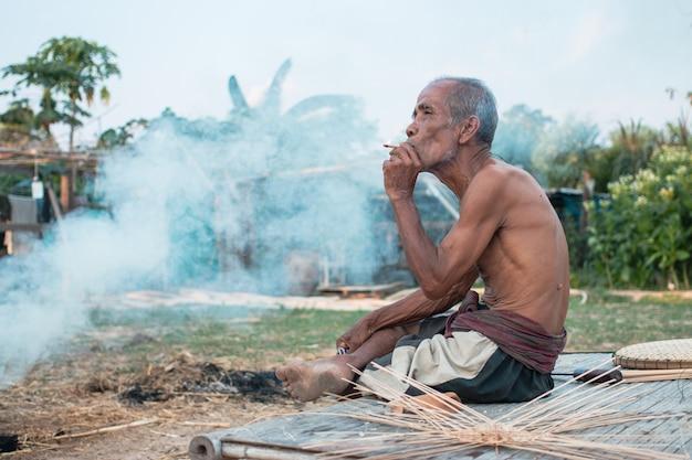 Пожилой мужчина сидел дым
