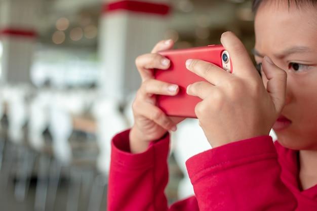 水平位置でスマートフォンを保持している小さな男の子
