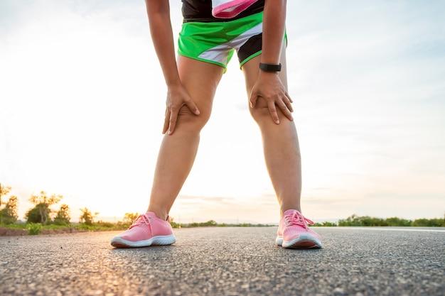 日没時に丘の中腹の道に沿って女性が走って運動しています。