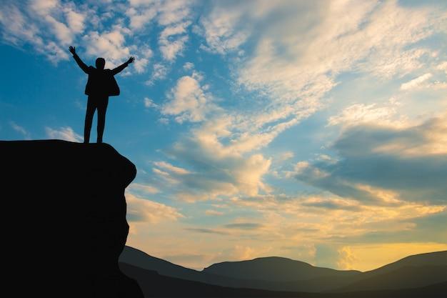 空と太陽の光、ビジネス、成功、リーダーシップ、達成および人々の上の山の頂上の男のシルエット