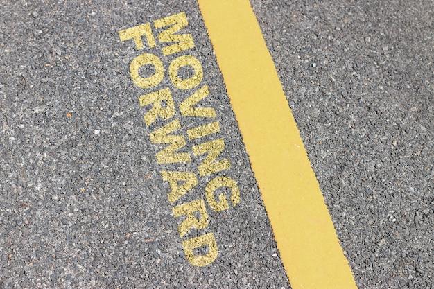アスファルト道路には黄色のストライプ、インスピレーションの活版印刷の引用があります。