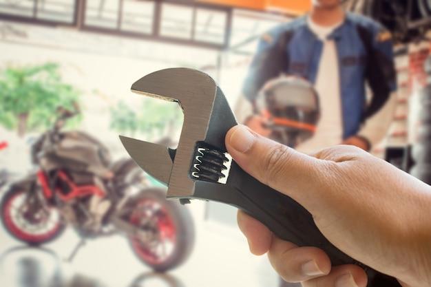 Рука человека держит инструмент обслуживания мотоцикла. концепции обслуживания перед поездкой