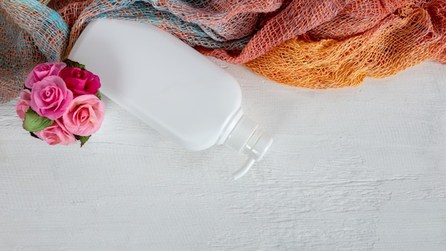 Косметическая бутылка может распылитель контейнер. диспенсер для сливок, супов, пен и другой косметики. косметический контейнер на белом деревянном и красивом ситце.