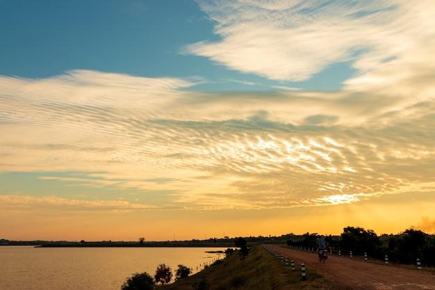 Старые люди ездят на велосипедах на обочине озера, красивые золотые небо облака с закатом. красивое небо .