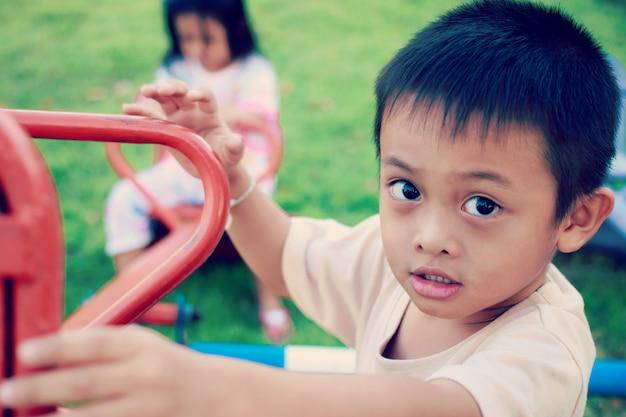 アジアの子供たちが朝の日差しの中で遊び場で遊んで