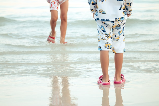 男の子と女の子は海で遊んで喜んでいます。家族の休日に
