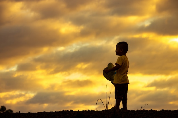 夕焼け空に孤独な子供のシルエット。