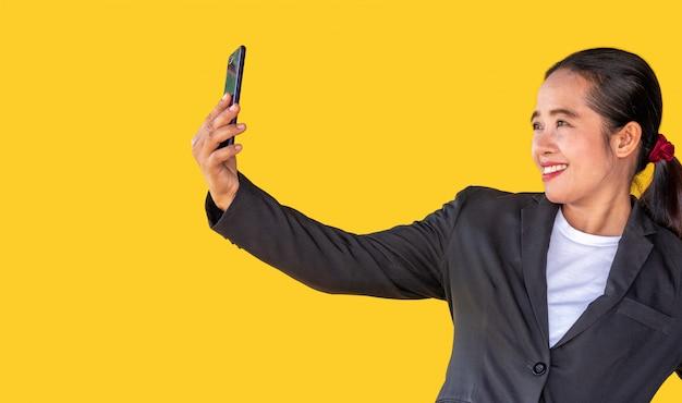 ビジネスの女性は、黄色の背景でスマートフォンを使用してビデオ通話を発信します