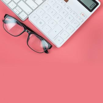 Вид сверху женское рабочее место, клавиатура компьютера, белый калькулятор и очки на ярко-розовом фоне.