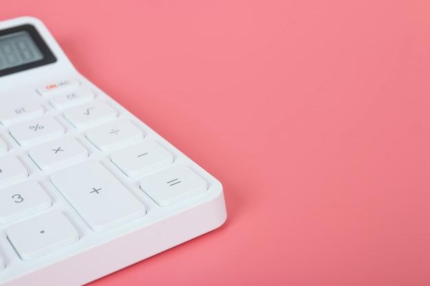 Белый калькулятор на ярко-розовом фоне, маркетинговые и финансовые концепции