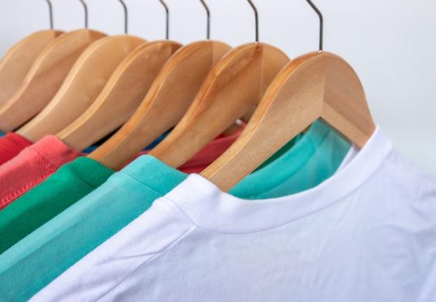 Фасонируйте футболку на шкафе одежды - крупный план яркого красочного шкафа на деревянных вешалках в шкафе магазина.