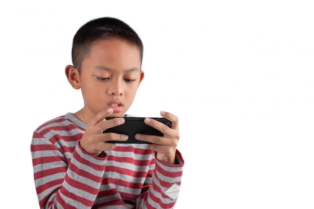 アジアの少年は彼のスマートフォンでゲームをしています。