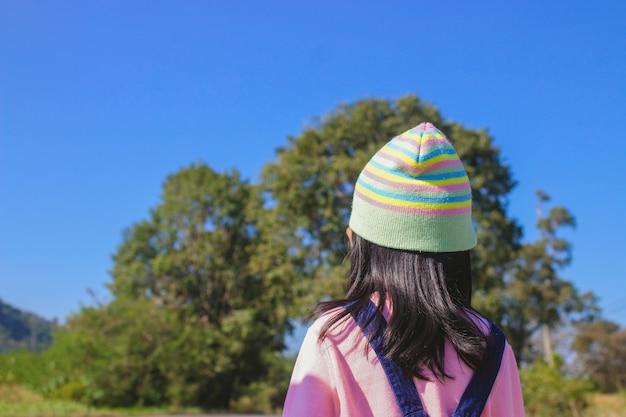 Маленькая детская девочка на фоне лесных деревьев на голубом небе