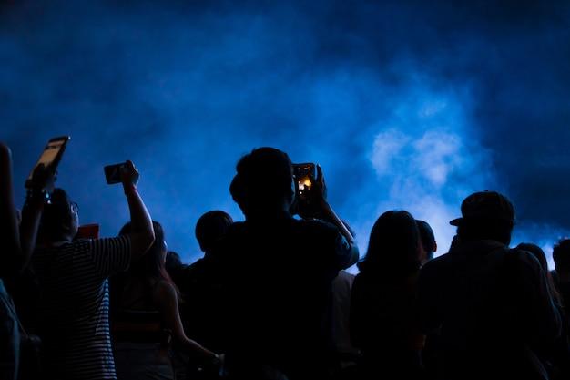 スマートフォンを持つ手は、ライブ音楽祭、コンサートステージの撮影を記録します