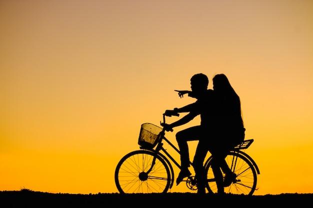 Силуэты пар и велосипед на закате небо