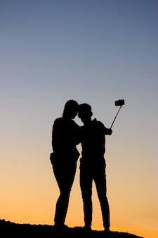 Силуэты мужчина и женщина, принимая селфи с смартфон на закат небо