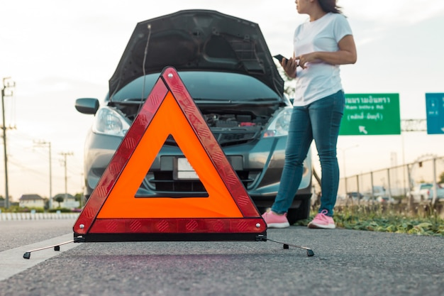 携帯電話を使用してフードを開く彼女の車の写真を撮る女性。