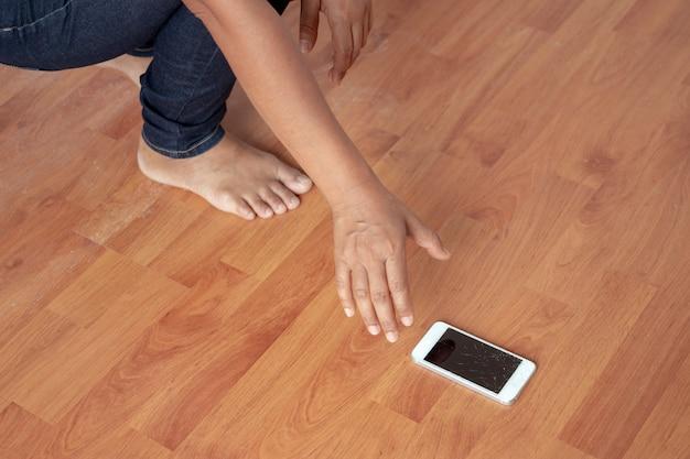 女性は家の床に落ちた電話を壊してしまった。