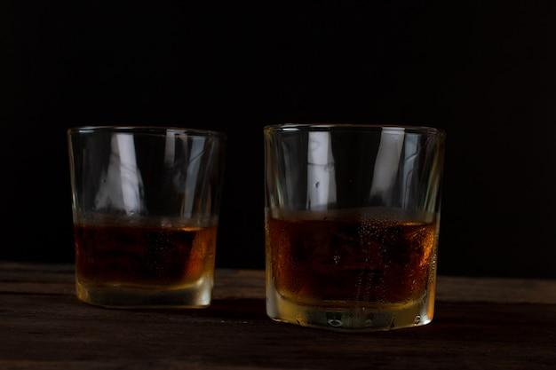 木製のテーブルの上の氷とアルコールスコッチウイスキーのガラス