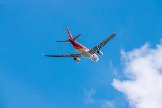 飛行機は青い空の雲に国際空港から離陸します。