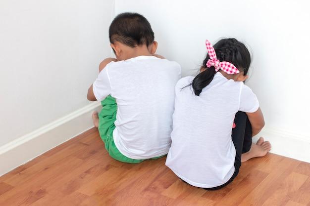 Мальчики и девочки сидят перед стеной в углу комнаты