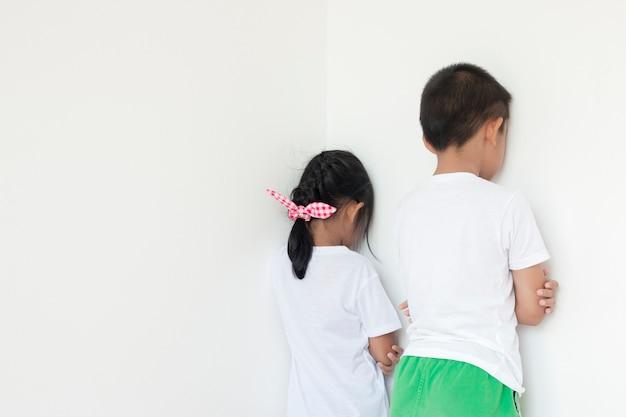 部屋の隅の壁の前に立っている男の子と女の子