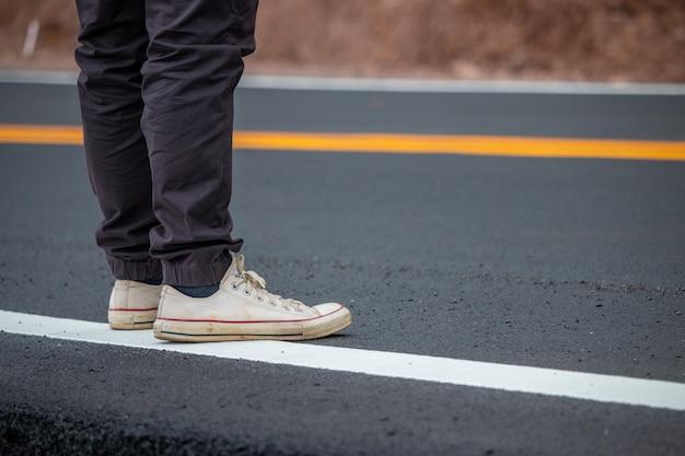 黄色い線で通りを歩いてスニーカーを着ている男性。