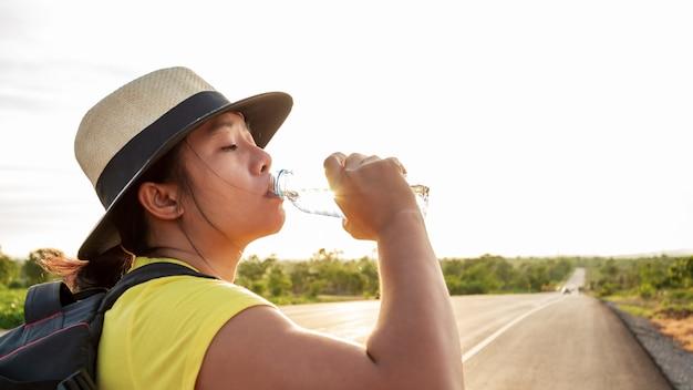 女性のバックパック観光客、高速道路で水を飲み、太陽の金色の光で。