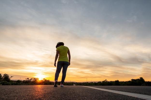 旅行に高速道路に沿って立っている日没時にジーンズ、スニーカー、帽子をかぶっている女性