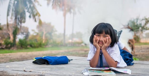Счастливый азиатский студент девушки в сельской местности