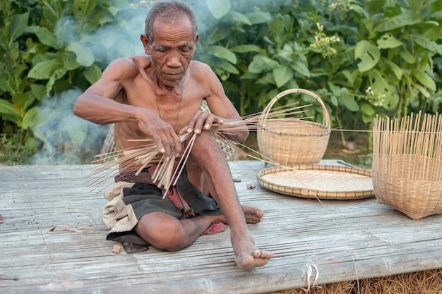 Дядя азиатский старик с плетеными инструментами.